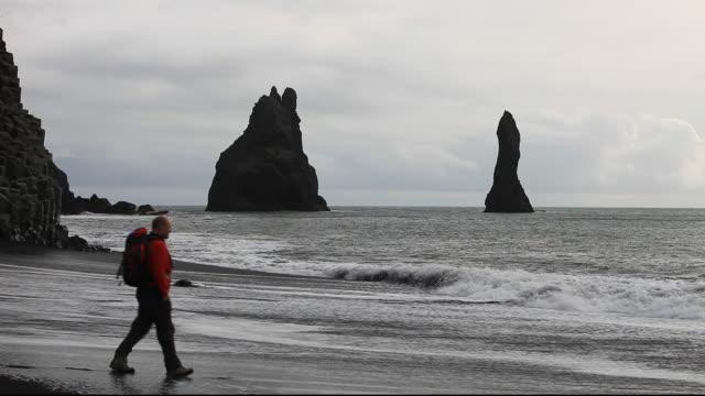 a man dodging waves on a black volcanic sand beach  near vik on iceland's south coast. - dyrholaey stock videos & royalty-free footage