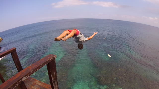 a man does a backflip and cliff jumping into the green sea to go surfing. - klippe stock-videos und b-roll-filmmaterial