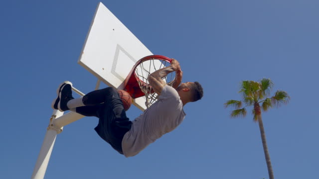 a man does a slam dunk while playing one-on-one basketball hoops on a beach court. - shooting baskets stock videos and b-roll footage