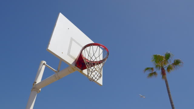 A man does a slam dunk while playing one-on-one basketball hoops on a beach court.