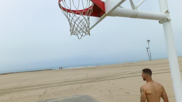 a man does a slam dunk while playing one-on-one basketball hoops on a beach court. - mindre än 10 sekunder bildbanksvideor och videomaterial från bakom kulisserna