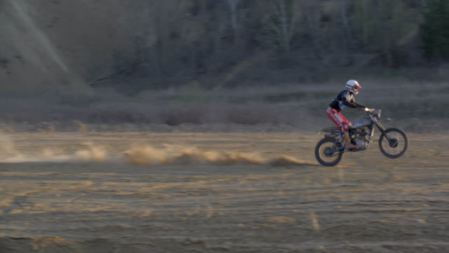man does a wheelie trick while racing and riding motocross motorcycles on a dirt off road. - slow motion - off road racing stock videos & royalty-free footage