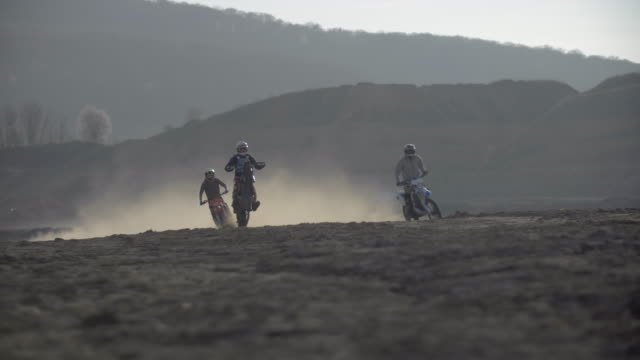 A man does a wheelie trick while riding and racing motocross motorcycles in a race on a dirt off road. - Slow Motion