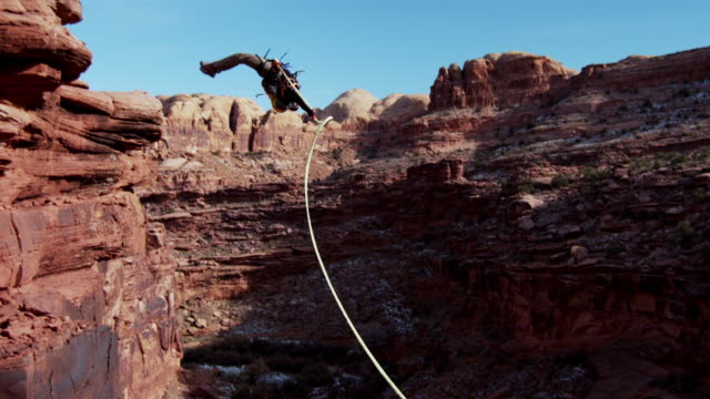 ws td pan slo mo man does  back flip off cliff in desert / moab, utah, united states   - klippe stock-videos und b-roll-filmmaterial