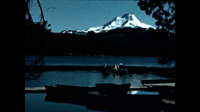 a man does some recreational fishing on lost lake with a view of little tahoma peak in mount rainier national park - mt rainier national park stock videos & royalty-free footage