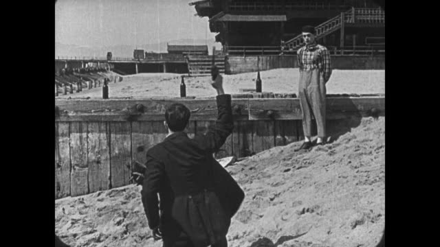 1921 Man (Buster Keaton) does target practice at beach