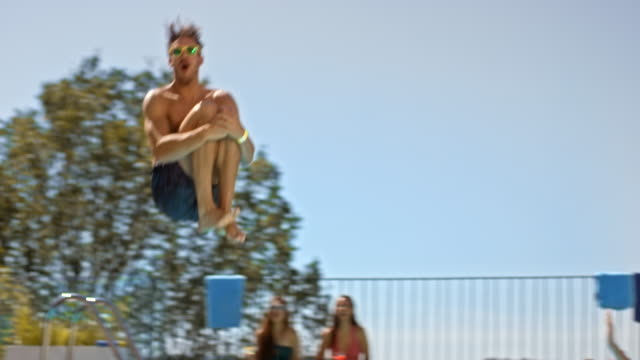 slo mo ds man doing a cannonball jump into the water at a pool party on a hot day - tuffarsi video stock e b–roll