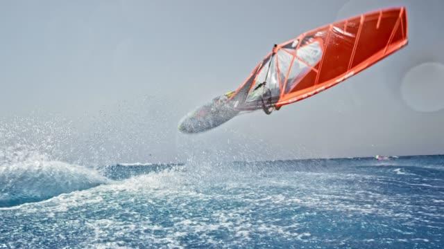 slo-mo-mann tut einen flip mit seiner windsurf bei sonnenschein - extremsport stock-videos und b-roll-filmmaterial