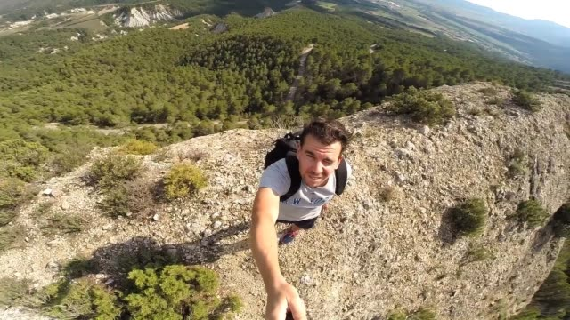 Man doing a selfie video on the top of a cliff.