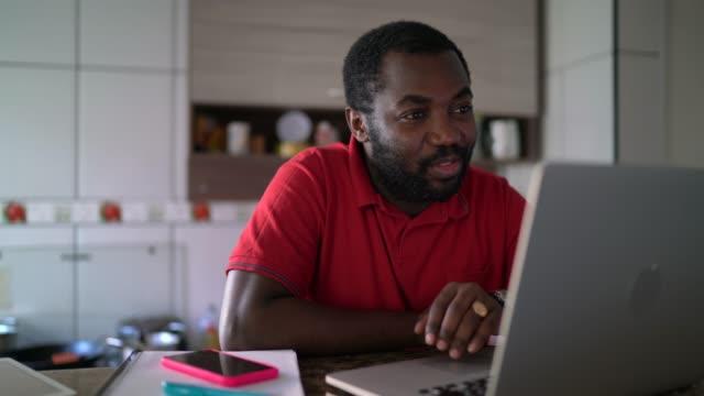 vídeos de stock, filmes e b-roll de homem fazendo uma chamada de vídeo em casa usando tablet digital - distante