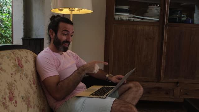 vídeos de stock, filmes e b-roll de homem fazendo uma chamada de vídeo usando laptop em casa - equipamento de mídia