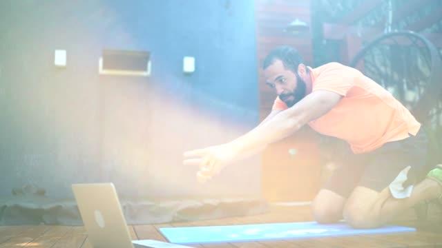 仮想エクササイズクラスをしている男、自宅でインストラクターと話す - エクササイズクラス点の映像素材/bロール