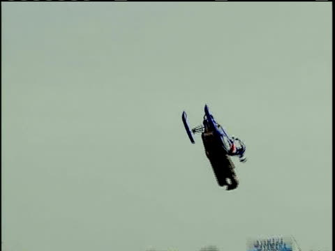 vidéos et rushes de ms, pan, man doing back flip on snowmobile riding off ramp, crashing on dirt mound, usa - procédé croisé