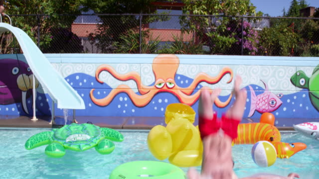 ms slo mo man doing backflip into outdoor swimming pool filled with inflatable pool toys friend sliding down water slide in background - pantaloncino da bagno video stock e b–roll