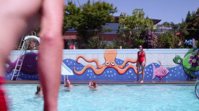 ms slo mo man doing backflip into outdoor swimming pool on summer afternoon during party - pantaloncino da bagno video stock e b–roll