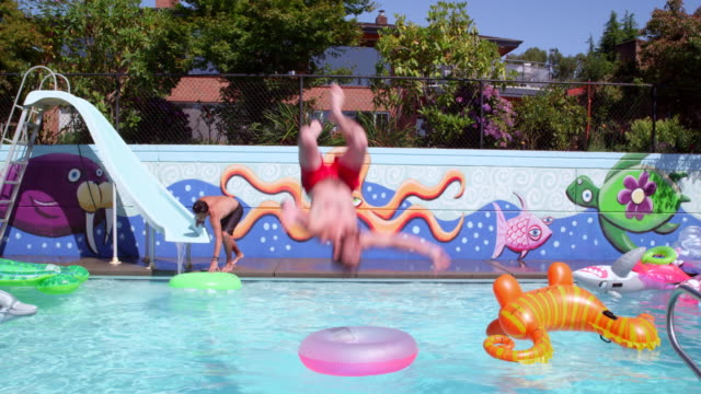 ms slo mo man doing backflip over inflatable inner tube in outdoor swimming pool on summer afternoon - pantaloncino da bagno video stock e b–roll