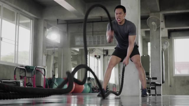 (Slow motion) Man doing battle ropes exercise in a fitness gym.