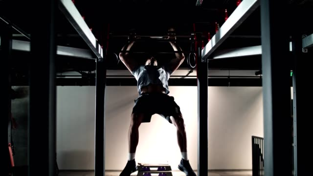man doing body weight exercise in the gym - hoisting stock videos & royalty-free footage
