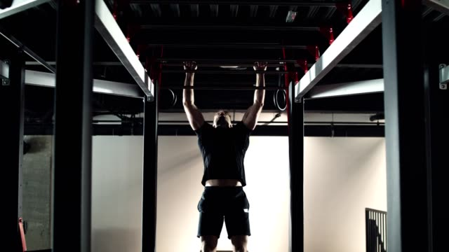 man doing body weight exercise in the gym - horizontal bar stock videos and b-roll footage