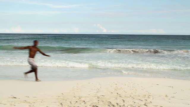 vídeos de stock, filmes e b-roll de man doing cartwheel on sandy beach - tulum méxico