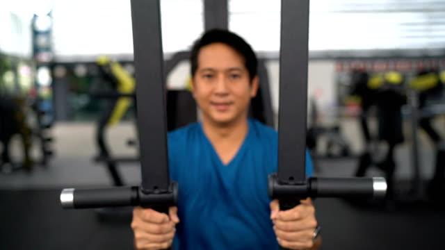 stockvideo's en b-roll-footage met man je borst oefening doet met behulp van de training computer - grote borstspier