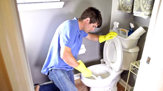 Man doing chores, cleaning toilet