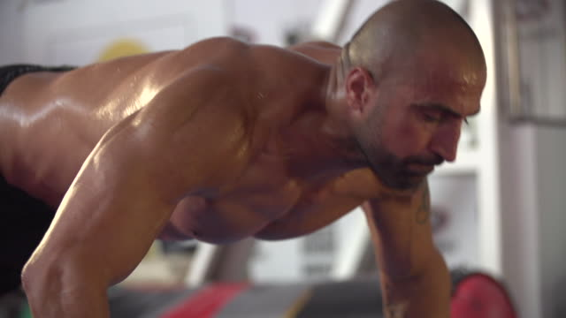 man doing clapping push-ups and gym workout at the gym.  - slow motion - 1920x1080 - filmed at 200 fps - 自重トレーニング点の映像素材/bロール
