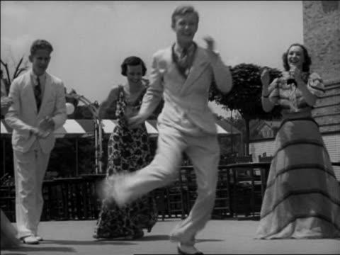 "B/W 1937 man doing crazy leg kicks while dancing ""Big Apple"" in circle outdoors / Washington, DC / newsreel"