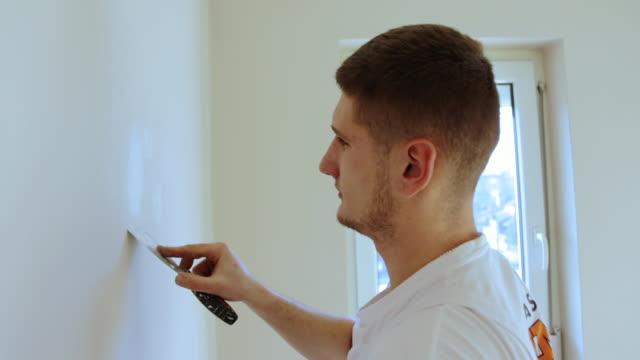 アパートでdiyプロジェクトをしている男 - 調理用へら類点の映像素材/bロール