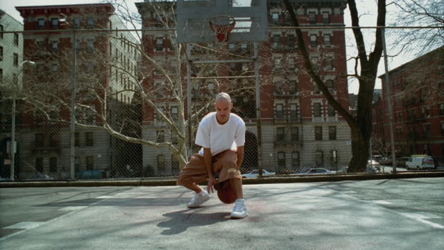 WS Man doing dribbling tricks with basketball on Morningside Park basketball court/ Harlem, New York