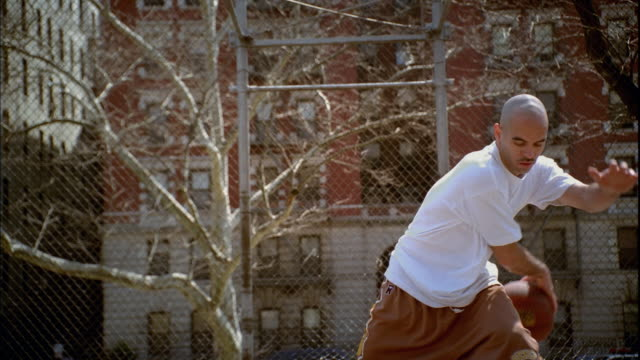 ws man doing dribbling tricks with basketball on morningside park basketball court/ harlem, new york  - t shirt stock videos & royalty-free footage
