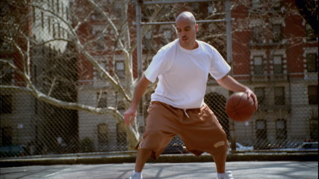 vídeos y material grabado en eventos de stock de ws man doing dribbling tricks with basketball on morningside park basketball court/ zip ms man's legs as he dribbles ball between them/ harlem, new york  - camiseta