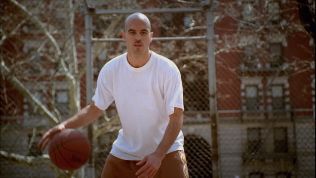 ws man doing dribbling tricks with basketball on morningside park basketball court/ zip ms man's legs as he dribbles ball between them/ harlem, new york  - t shirt stock videos & royalty-free footage
