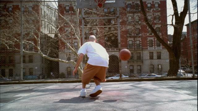WS Man doing dribbling tricks with basketball on Morningside Park basketball court/ ZIP MS Man's legs as he dribbles ball between them/ Harlem, New York