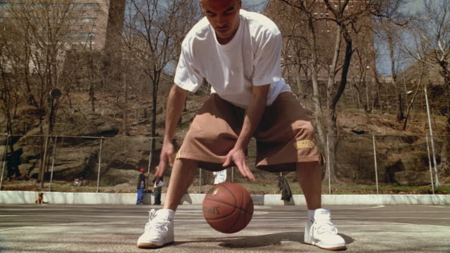 ws man doing dribbling tricks with basketball on morningside park basketball court/ zi ms man's legs as he dribbles ball between them/ harlem, new york  - moving down stock videos & royalty-free footage