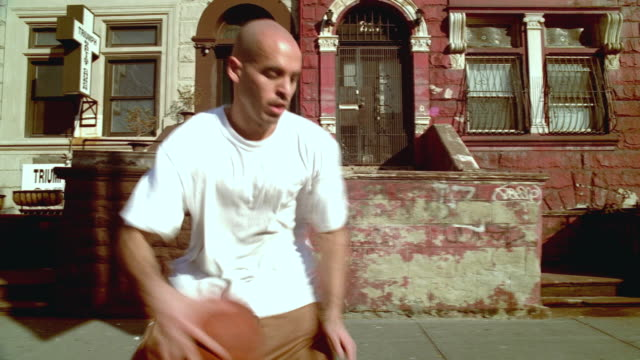 ms pan man doing dribbling tricks with basketball past city buildings/ harlem, new york  - front stoop stock videos and b-roll footage
