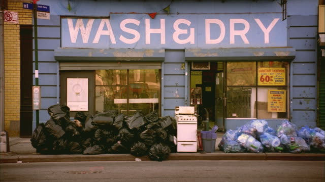 ws pan man doing dribbling tricks with basketball past laundromat and piles of trash on curb/ harlem, new york  - waschsalon stock-videos und b-roll-filmmaterial