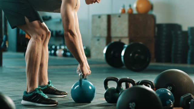 man doing exercise with kettlebell in gym - kettlebell stock videos & royalty-free footage