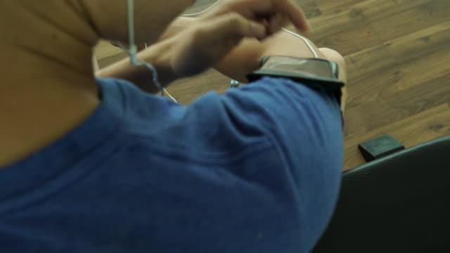 Mann Übungen im Fitnessstudio mit einem Smartphone