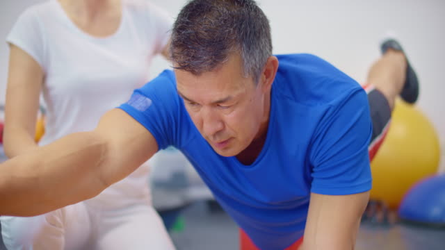 slo mo man doing exercises under the supervision of a physical therapist - two people stock videos & royalty-free footage