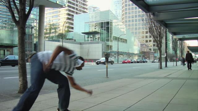 SLO MO MS Man doing flip on downtown sidewalk, Vancouver, British Columbia, Canada