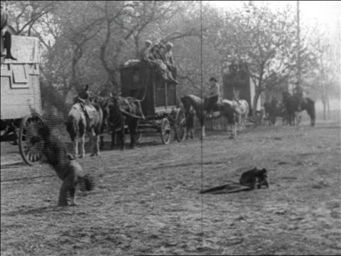 b/w 1925 man (harry langdon) doing flipflops as men on line of wagons watch / feature - 1925 stock videos & royalty-free footage