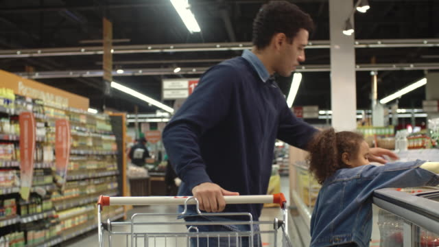 Man doing grocery shopping with daughter