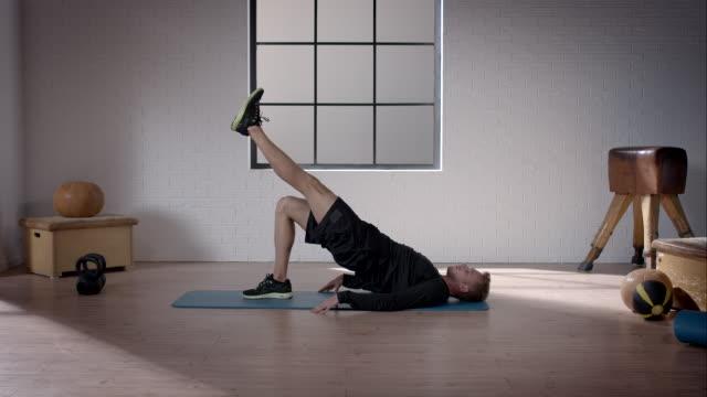 mann bei seinem training im fitnessraum (becken hebe ein bein - knochen im beckenbereich stock-videos und b-roll-filmmaterial
