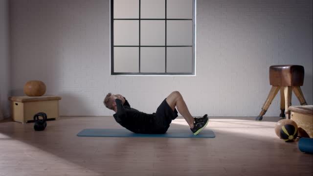 mann bei seinem training im fitnessraum (bauchpressen - rumpfbeuge stock-videos und b-roll-filmmaterial