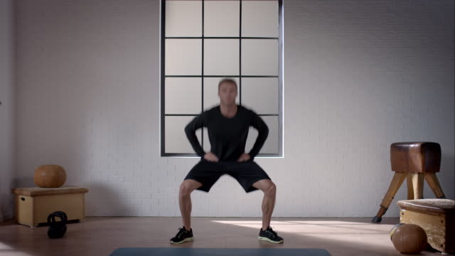 man doing his workout in gym (jumping jacks squat) - star jump stock videos & royalty-free footage