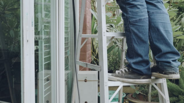 a man doing home maintenance - ladder stock videos and b-roll footage