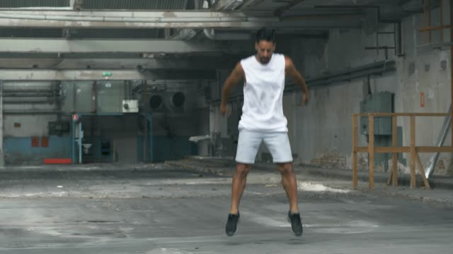 Man doing Jumping Exercises in an Abandoned Warehouse