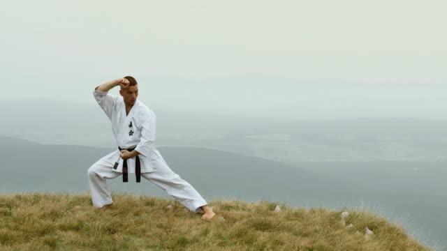 vídeos de stock, filmes e b-roll de ws cs man doing karate at edge of mountain / vipava, nature park nanos, slovenia - karate