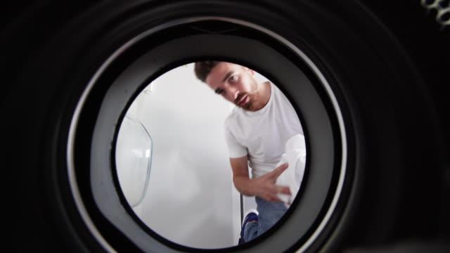 vídeos de stock e filmes b-roll de man doing laundry in a gender equality situation - calças de ganga